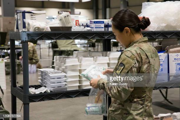 Military personnel including Jina Evans from Los Angeles CA set up the 627th Hospital Center field hospital at CenturyLink Event Center on March 31...