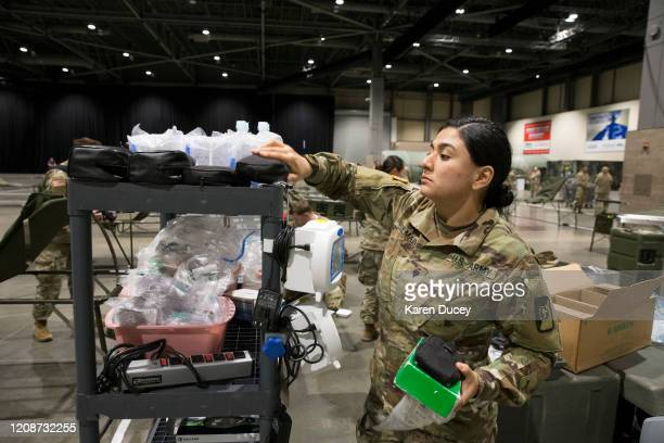 Military personnel including Sara Dulmaine from Worcester Massachusetts set up the 627th Hospital Center field hospital at CenturyLink Event Center...