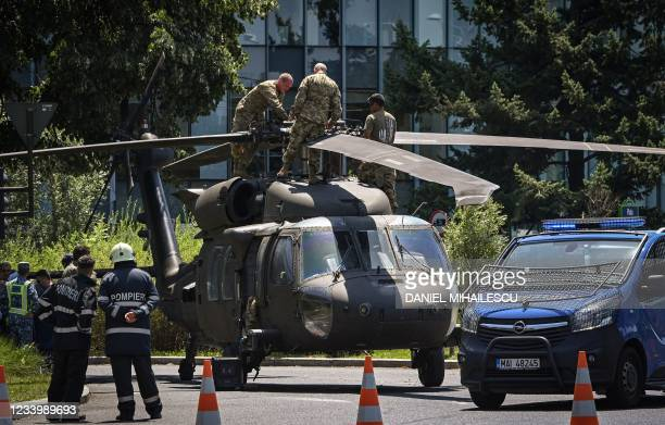 Military personnel inspect a Black Hawk helicopter at Charles de Gaulle square in Bucharest on July 15 after it forced landed, apparentlly due to...