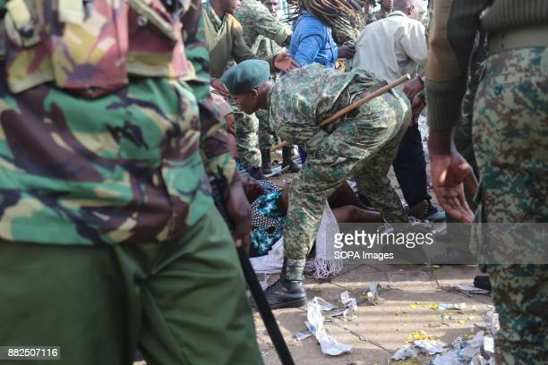 Military personnel lift up a woman who fell over in a stampede at Kasarani Stadium as the crowd forced its way into the stadium during the swearing...
