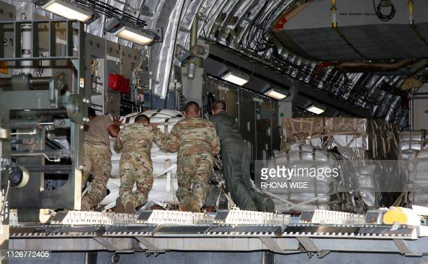 US military personnel load a C17 cargo plane with food water and medicine for a humanitarian mission to Colombia to aid Venezuelans at the Homestead...