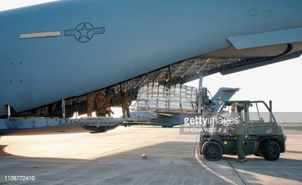 TOPSHOT US military personnel load a C17 cargo plane with food water and medicine for a humanitarian mission to Colombia to aid Venezuelans at the...
