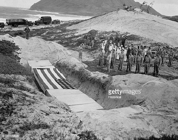 Military personnel pay their respects beside the mass grave of 15 officers and others killed in the bombing attack at Pearl Harbor on December 7 1941...