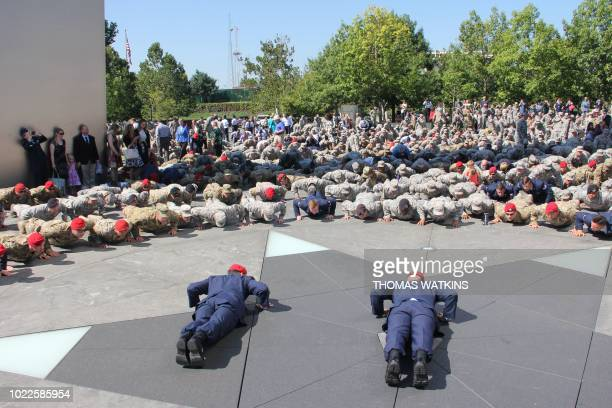 Military personnel perform push ups at the Air Force Memorial on August 24 in Arlington Virginia during a ceremony commemorating the Medal of Honor...