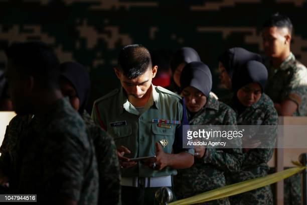 Military personnel queuing up to cast their ballots during early voting for the Port Dickson Parliament byelection at the Army Basic Training Centre...