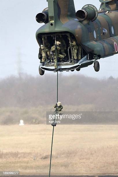 Military personnel rappel down from a Chinook helicopter during the annual new year parachute exercise at Japan Ground SelfDefense Force Narashino...