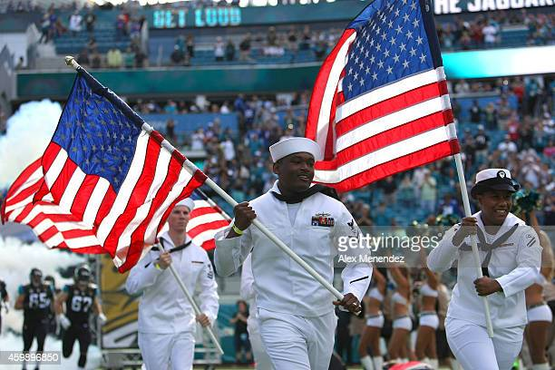 Military personnel run out with US flags for player introductions during an NFL football game between the New York Giants and the Jacksonville...