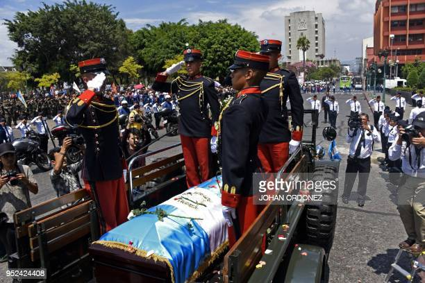 Military personnel salute during the funeral of former Guatemalan President and Guatemala City Mayor, Alvaro Arzu, at Culture Palace in Guatemala...