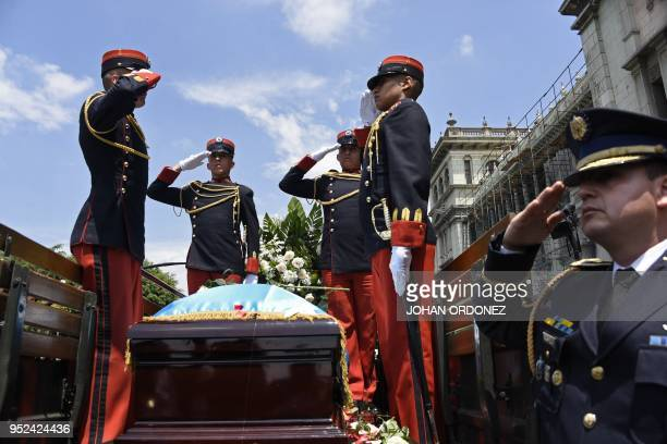 Military personnel salute during the funeral of former Guatemalan President and Guatemala City Mayor Alvaro Arzu at Culture Palace in Guatemala City...