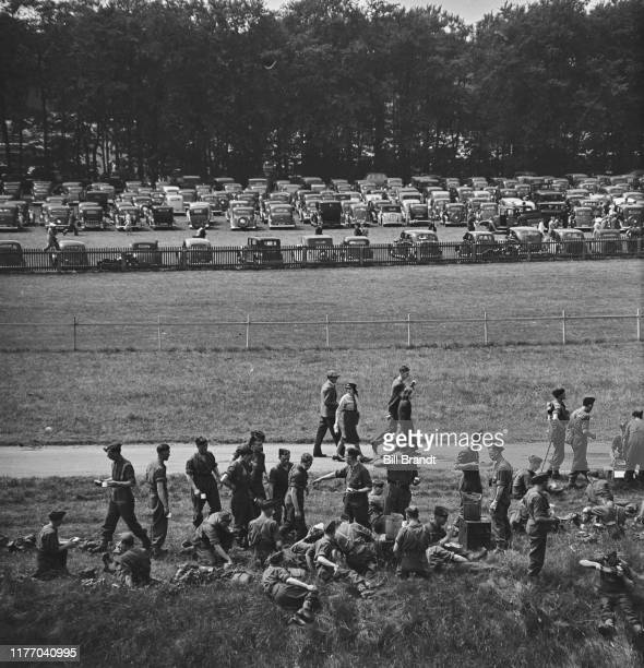 Military personnel sit on the grass preparing a meal and to watch the wartime New Derby run at Newmarket racecourse in Suffolk 18th June 1941 Owen...