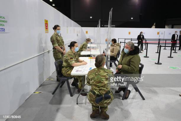 Military personnel speak with Joanne McLaren as she arrives for a clinic at the Winter Gardens in Blackpool, which has been converted for use as a...