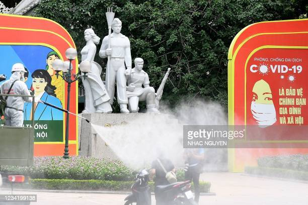 Military personnel spray liquid disinfectant along a street near the popular Hoan Kiem lake in Hanoi on July 26, 2021 as a preventive measure to stop...
