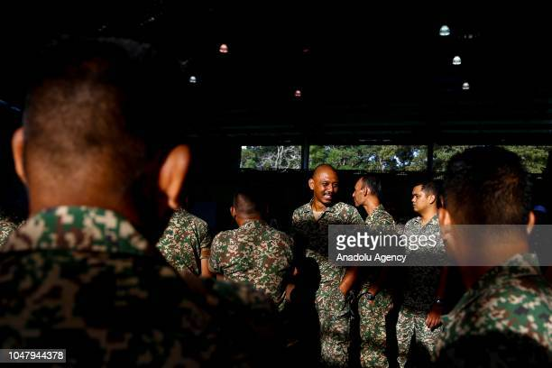 Military personnel stand in line to cast their ballots early voting for the Port Dickson Parliament byelection at the Army Basic Training Centre in...