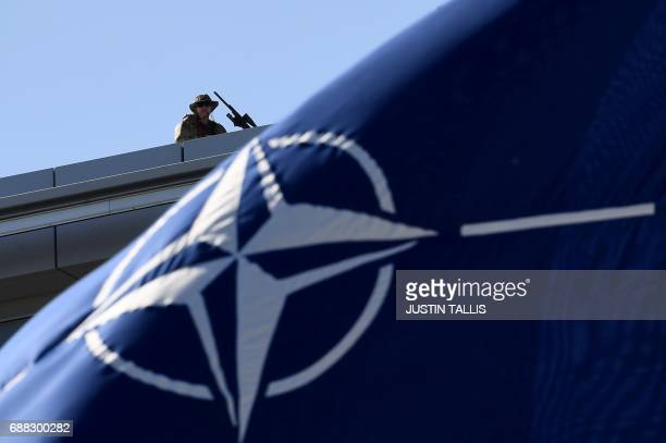 A military personnel stands guard on top of the roof during the NATO summit ceremony at the NATO headquarters in Brussels on May 25 2017 / AFP PHOTO...