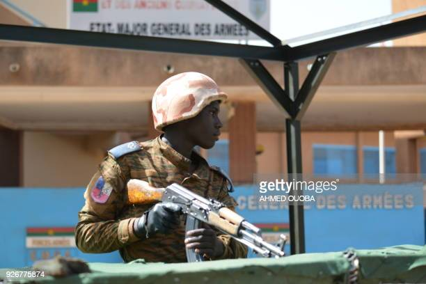 Military personnel stands outside the headquarters of the country's defence forces in Ouagadougou on March 3, 2018 a day after dozens of people were...