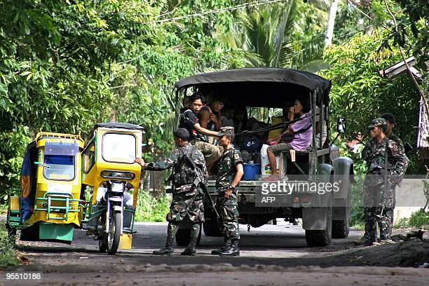 Military personnel stop a tricycle driver as forced evacuations for residents living at the foot of the Mayon volcano have been implemented in near...