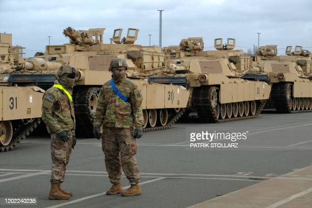 Military personnel unload M1 Abrams Fighting tanks of the 2nd Brigade Combat Team, 3rd Infantry Division, as US military equipment arrives to the...
