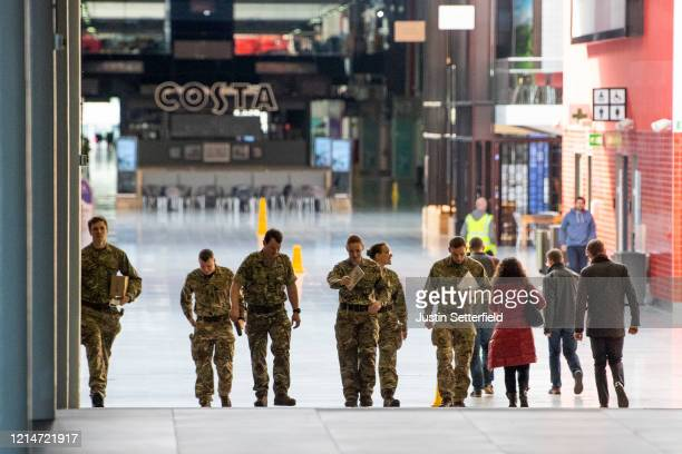 Military personnel walk inside the Excel Centre in East London on March 25 2020 in London England The field hospital will initially contain 500 beds...