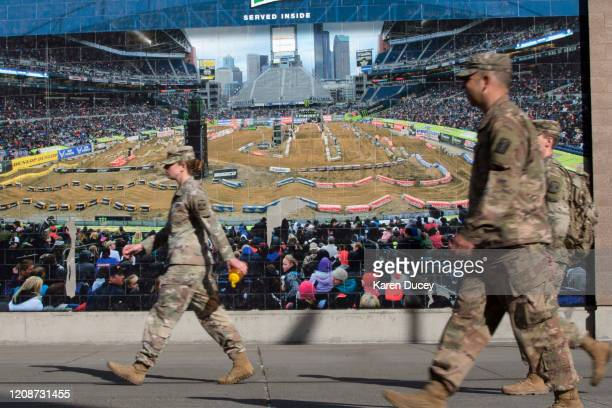 Military personnel walk past a mural outside the 627th Hospital Center field hospital at CenturyLink Event Center on March 31 2020 in Seattle...