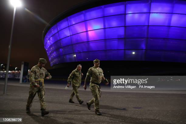 Military personnel walk past The SSE Hydro in Glasgow, which is lit up in blue in a gesture of thanks to the hardworking NHS staff who are trying to...