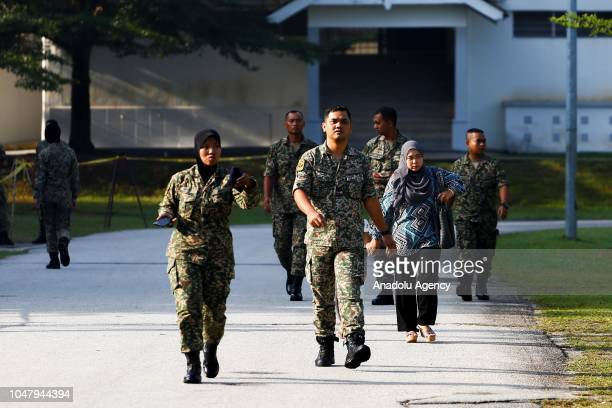 Military personnel walk up to cast their ballots during early voting for the Port Dickson Parliament byelection at the Army Basic Training Centre in...