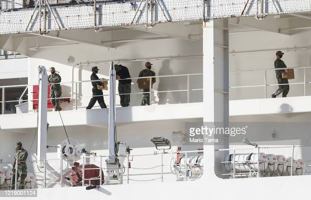 Military personnel wearing face masks work aboard the USNS Mercy Navy hospital ship docked in the Port of Los Angeles amidst the coronavirus pandemic...