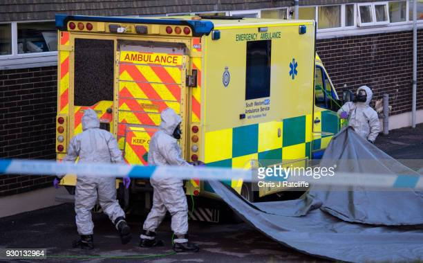 Military personnel wearing protective suits cover a second ambulance after removing another from Salisbury ambulance station as they continue...