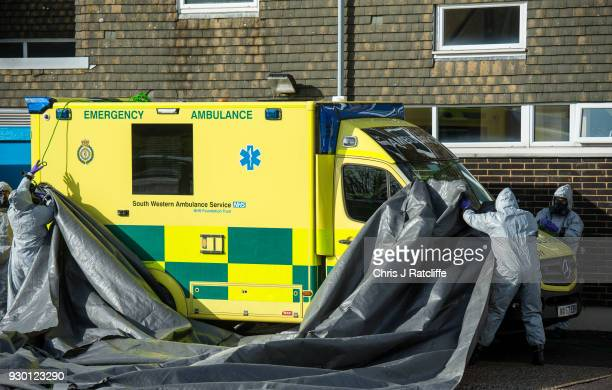 Military personnel wearing protective suits cover two ambulances with tarpaulin as they prepare to remove them from Salisbury ambulance station as...