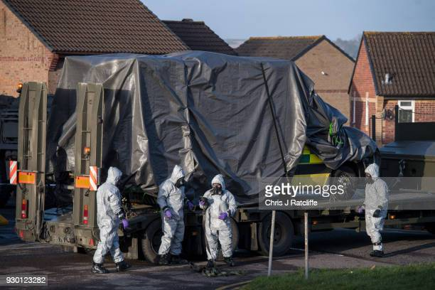 Military personnel wearing protective suits load an ambulance as they prepare to remove it from Salisbury ambulance station as they continue...