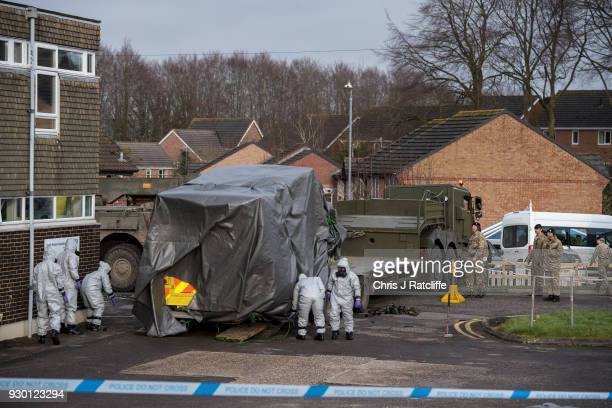 Military personnel wearing protective suits load an ambulance on to a truck as they prepare to remove it from Salisbury ambulance station as they...