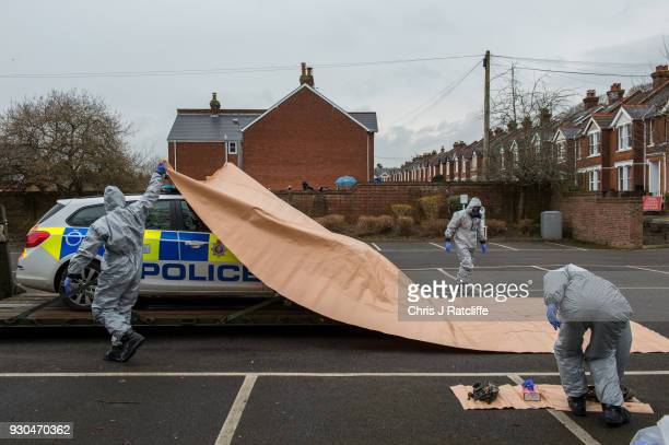 Military personnel wearing protective suits remove a police car and other vehicles from a public park as they continue investigations into the...