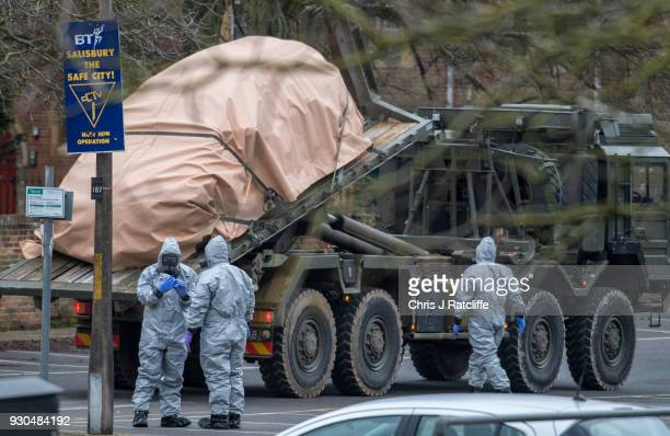 Military personnel wearing protective suits remove a police car and other vehicles from a public car park as they continue investigations into the...