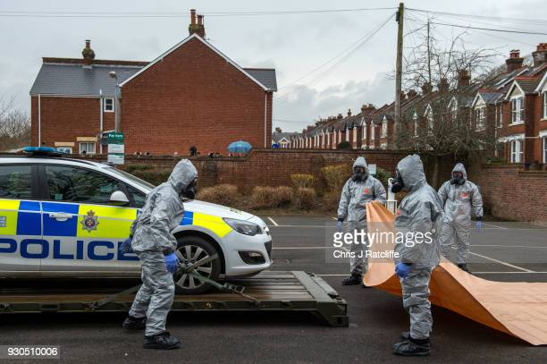 Military personnel wearing protective suits remove a police car and other vehicles from a public park park as they continue investigations into the...