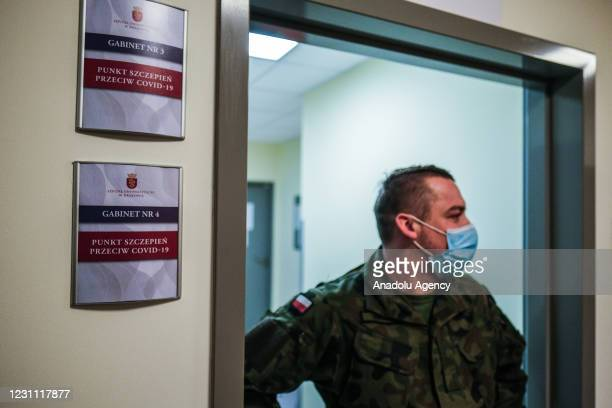 Military personnel wears a protective face masks and helps during the a Oxford-AstraZeneca COVID-19 vaccination of teachers at the Krakow University...