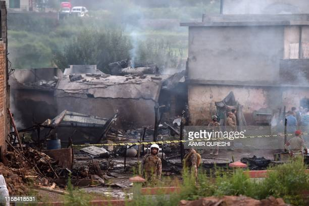 Military personnel work at the scene where a Pakistani Army Aviation Corps aircraft crashed in Rawalpindi on July 30 2019 Fifteen people were killed...