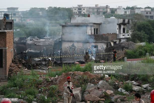 TOPSHOT Military personnel work at the scene where a Pakistani Army Aviation Corps aircraft crashed in Rawalpindi on July 30 2019 Fifteen people were...