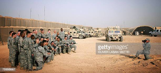 A US military photographer takes a picture of two platoons at Camp Warhorse in Baquba 60 kms north of Baghdad 04 August 2007 Five US soldiers have...