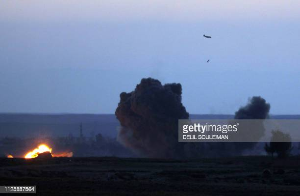 TOPSHOT A military plane with the USbacked coalition against the Islamic State group releases a bomb over the embattled village of Baghouz on...