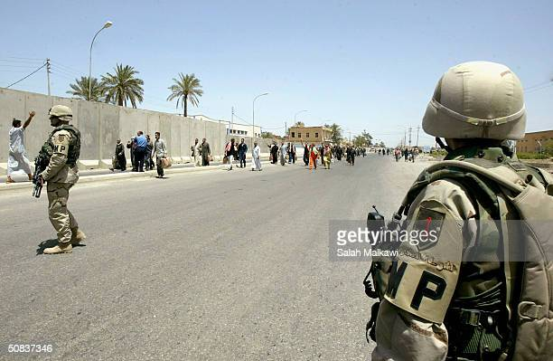 BA'QOUBAH IRAQ MAY 14 Military Plolice look on as prisoners walk the streets after being released from Abu Ghraib prison on May 14 2004 in Ba'qoubah...