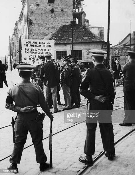 Military police guard the checkpoint between zones in postwar Berlin circa 1955 The sign reads 'You are leaving the American sector' in English...