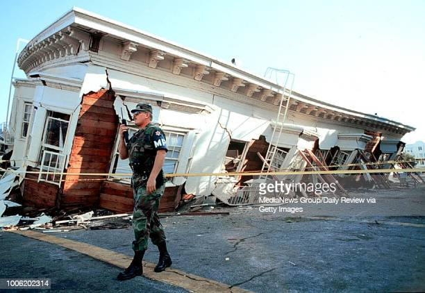 Military police guard the remains of a collapsed building on Divisidero and Beach Streets in San Francisco, on Oct. 18, 1989 a day after the Loma...