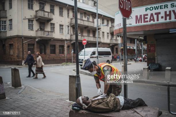 Military police officer from the South African National Defence Force , checks on a homeless man who overdosed, while on patrol in the streets of...