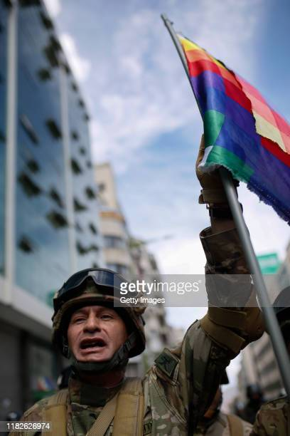 A military police officer holds a Whipala flag during a protest on November 15 2019 in La Paz Bolivia Morales flew to Mexico alleging a coup under...