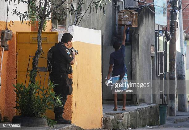Military Police officer holds his weapon as a man removes a birdcage hanging in front of a home in the Cidade de Deus 'City of God' favela community...