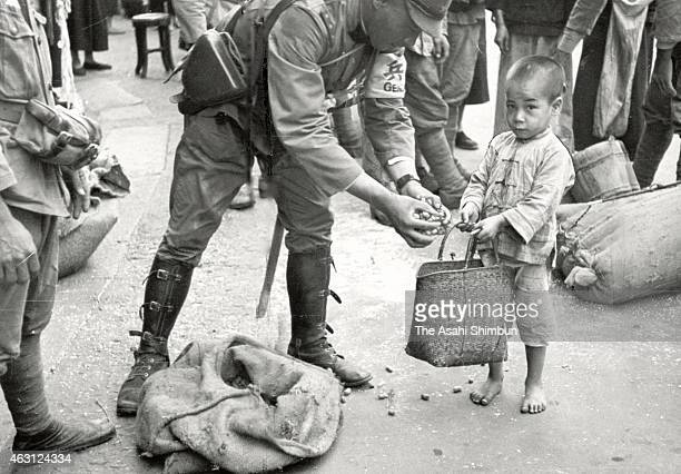 A military police officer of the Imperial Japanese Army provides peanuts to a local child at a city in Guangdong during SinoJapanese war on November...