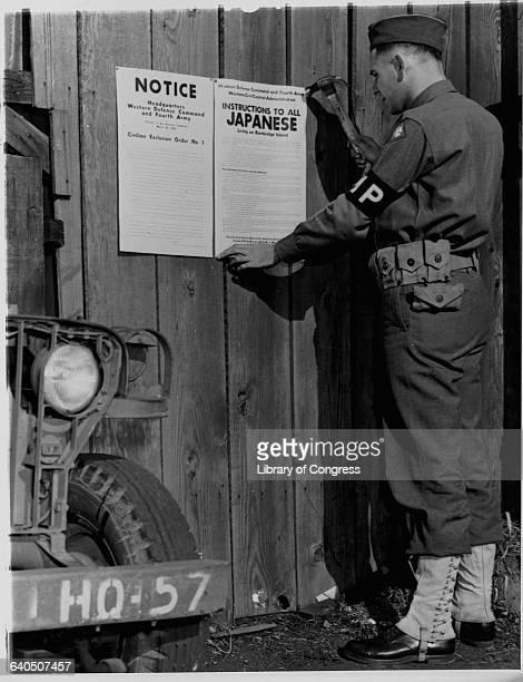 A military police officer posts Civilian Exclusion Order No 1 reguiring evacuation of Japanese living on Bainbridge Island Washington 1942