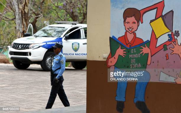A military police officer stands guard outside a school in Tegucigalpa on April 18 2018 Students are also victims of the prevailing insecurity in...