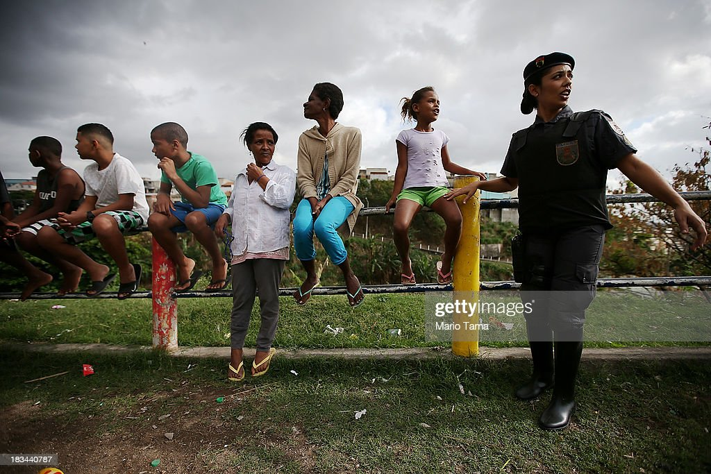 A military police officer (R) stands with residents during a 'pacification' operation in the favela complex of Lins de Vasconcelos, in the North Zone, on October 6, 2013 in Rio de Janeiro, Brazil. The favela complex, or shanty town, was previously controlled by drug traffickers and will now be occupied by the city's 35th UPP or 'Police Pacification Unit'. The favela pacifications are occurring amid Rio de Janeiro's efforts to improve security ahead of the 2014 FIFA World Cup and 2016 Olympic Games.