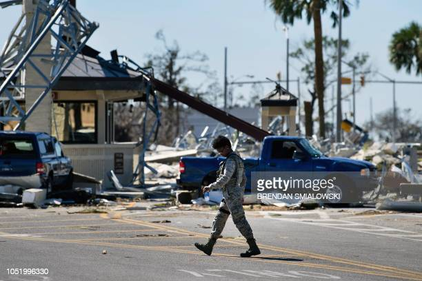 A military police officer walks near a destroyed gate in Tyndall Air Force Base in Florida in the aftermath of Hurricane Michael on October 12 2018...