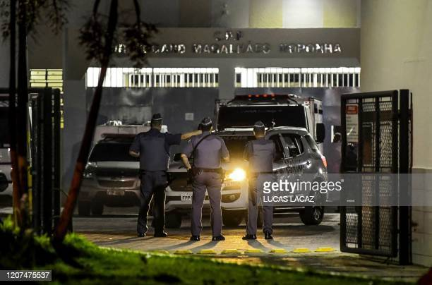 Military police officers are seen at the main entrance of the Doctor Edgar Magalhaes Noronha Penitentiary during a riot on early March 17 in...